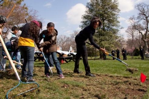 Michelle Obama rakes with the raking action